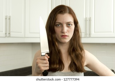 Young woman holds sharp knife in kitchen in an aggressive manner