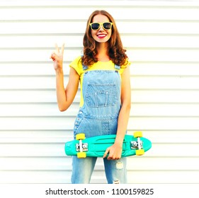 Young woman holds a skateboard having fun over a white background