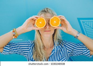 young woman holds two pieces of oranges covering her eyes.