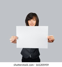 Young woman holds a white paper banner, space for text, focus on paper