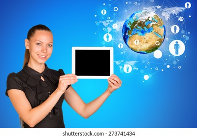 Young woman holging tablet looking at camera. Model of earth on blue background. Connection all over the world. Elements of this image furnished by NASA