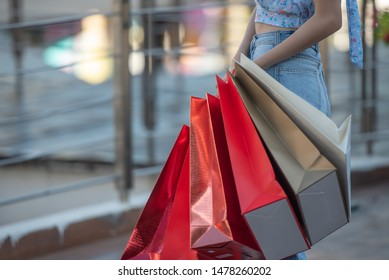 Young woman holing a lot of shopping bags buy things at shopping mall.