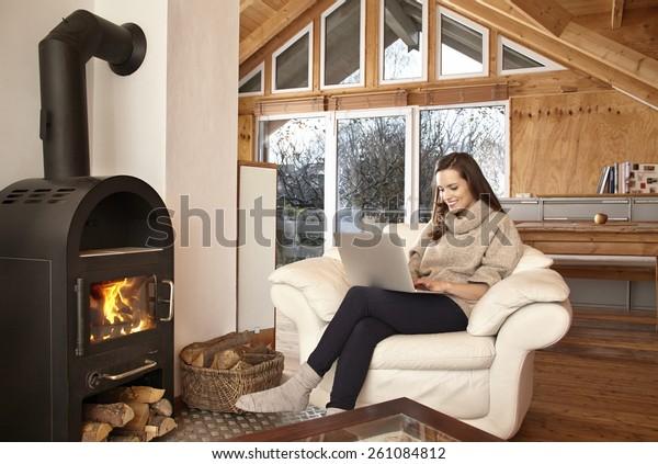Jeune femme à la maison en chaise avec ordinateur portable