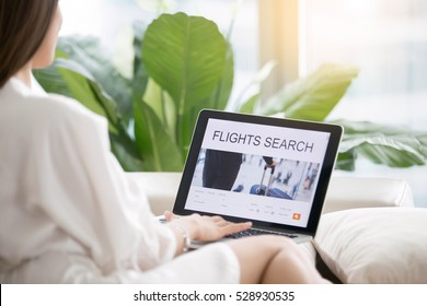 Young woman at home checking popular destinations on laptop, trying to get the cheapest flights, planning traveling for business, self-guided tour, last minute decision. View over the shoulder