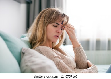 Young woman at home having headache, depressed girl with negative emotions