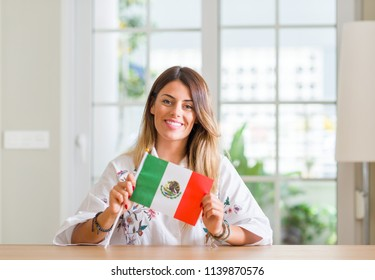 Young woman at home holding flag of Mexico with a happy face standing and smiling with a confident smile showing teeth