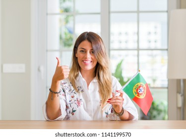 Young woman at home holding flag of Portugal happy with big smile doing ok sign, thumb up with fingers, excellent sign