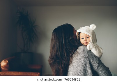 Young woman at home holding her cute little son. Mother carries the child in her arms.