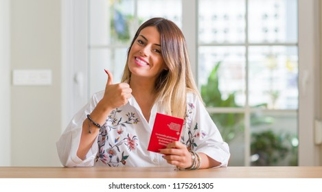Young woman at home holding a passport of Switzerland happy with big smile doing ok sign, thumb up with fingers, excellent sign