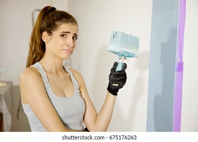 Young woman at home painting wall blue color