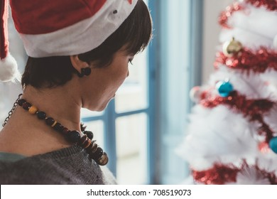Young woman at home preparing christmas tree - christmas, holiday, winter concept