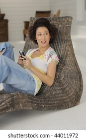 Young woman at home relaxing with cell phone.