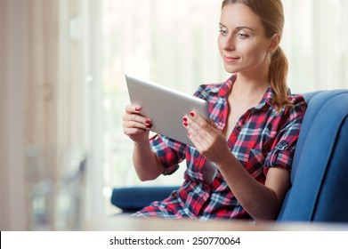 Young woman at home relaxing in her living room reading a digital tablet PC surf internet and work