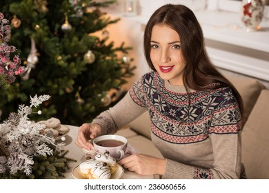 Young woman at home sipping tea from a cup and eating cookies while sitting on couch near Christmas tree
