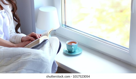 Young woman at home sitting near window relaxing in her living room reading book and drinking coffee or tea . Young woman at home