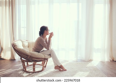 Young woman at home sitting on modern chair in front of window relaxing in her living room and drinking coffee or tea