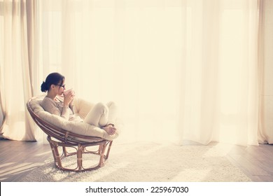 Young woman at home sitting on modern chair in front of window relaxing in her living room reading book and drinking coffee or tea, instagram toning