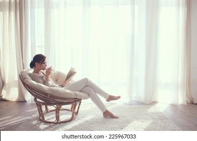Jeune femme à la maison assise sur une chaise moderne devant la fenêtre se relaxant dans son salon lisant un livre et buvant du café ou du thé