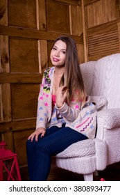 Young woman at home sitting on modern chair in her living room
