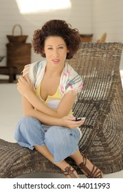 Young woman at home sitting on wicker chair with cell phone in hand.