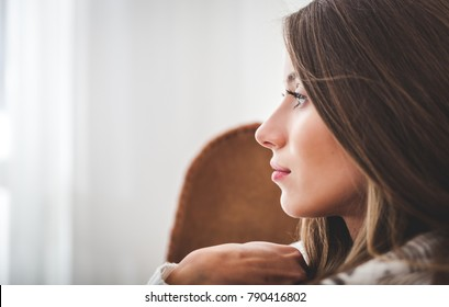 Young woman at home sitting on chair and thinking about something