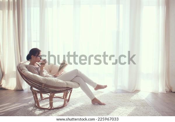 自宅の若い女性が、リビングルームで本を読み、コーヒーや紅茶を飲みながら窓の前のモダンな椅子に座る