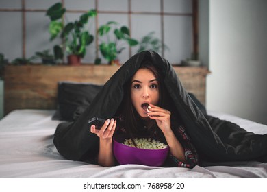 Young woman at home sofa couch in living room watching television scary horror movie or suspense thriller film or horrible news horrified holding remote controller in panic eating popcorn bowl