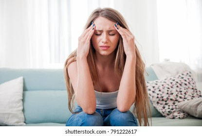 Young woman at home suffering from headache, emotions and stress