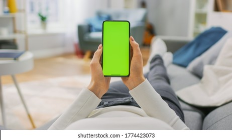 Young Woman at Home Uses Green Mock-up Screen Smartphone. She's Sitting On a Couch in His Cozy Living Room. Point of View Shot.