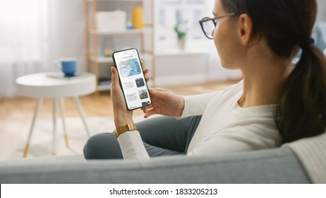 Young Woman at Home Uses Smartphone for Scrolling and Reading News about Technological Breakthroughs. She's Sitting On a Couch in Her Cozy Living Room. Over the Shoulder Shot