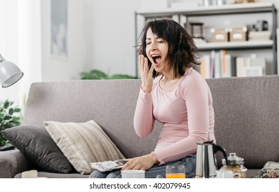 Young woman at home waking up after a bad night's sleep on the couch, she is yawning