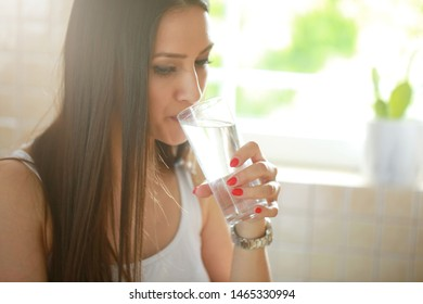 Young woman  at home while drinking water and hanging in phone. stock photo