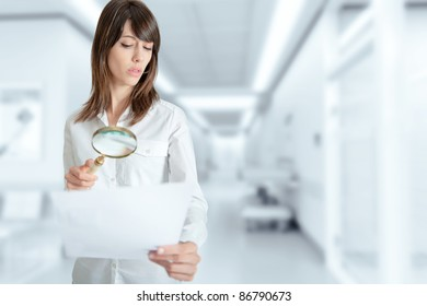 Young woman at the hospital examining a document with a magnifying glass
