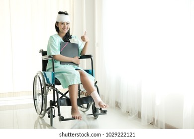 Young woman in hospital wheel chair. Happy smile as she got insurance money cover. Beautiful chinese woman. Medical, health insurance concept.