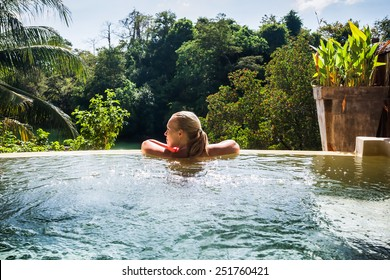 Young woman in hotel with private swimming pool