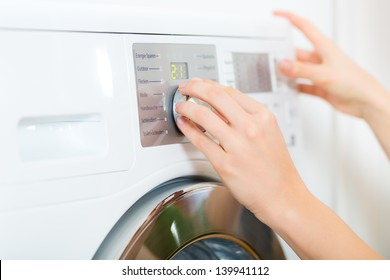 Young woman or housekeeper has a laundry day at home, she select the program