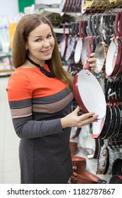 Young woman housewife buying new frying pan in hypermarket store for cooking, looking at camera