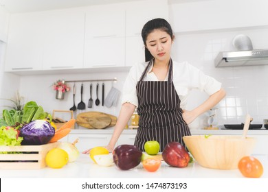 Young woman or housewife is tired of cooking, which consists of a variety of fruits and vegetables for the family.
