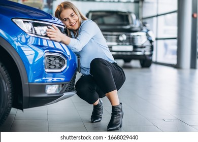 Young woman hugging a car in a c ar showroom