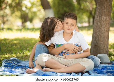 Young woman hugging with her 10 y.o. son and kissing him. They  are sitting on a blue picnic blanket in a park.