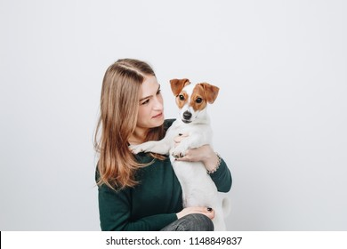 Young woman hugs her puppy jack russell terrier dog and looks at it. Love between dog and owner. Isolated on white background. Studio portrait.