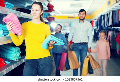 young woman with husband and daughters buying towels in shopping mall