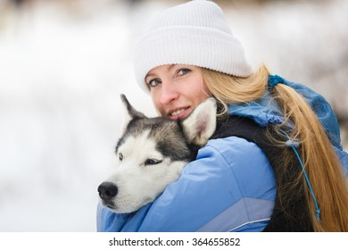 Young woman with husky dog in winter