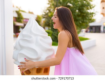 Young woman with ice cream cone in the summer city