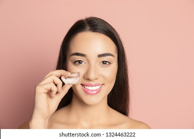 Young woman with ice cube on color background. Skin care