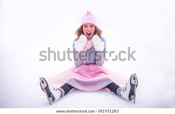 Young woman with ice skates siting on ice