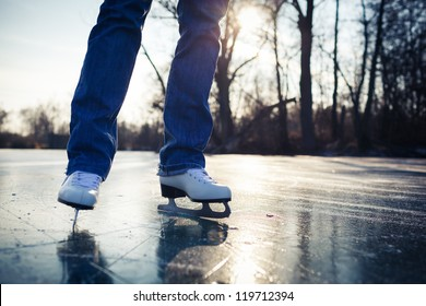 Young woman ice skating outdoors on a pond on a beautiful sunny day (selective focus)