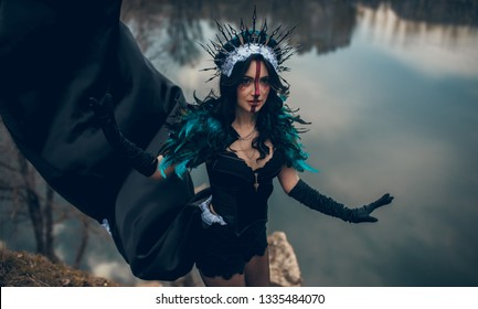 A young woman in the image of a fairy and a sorceress standing next to rocks over a lake with the reflection of the clouds in a black dress and a crown.