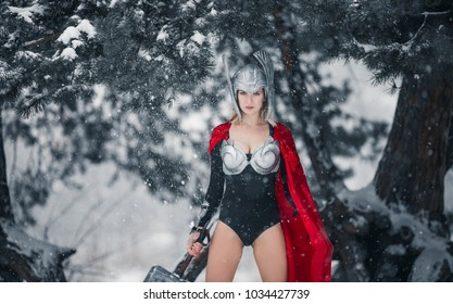Young woman in image of Germanic-Scandinavian God of thunder and storm stands with hammer in her hand against winter forest background. Cosplay.