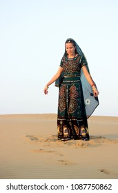 A young woman in Indian national clothes looks thoughtfully at the sand, standing under the setting sun in dunes of the Tar desert. Rajasthan, India.